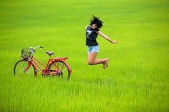 Glückliches Mädchen, das neben Fahrrad auf dem Paddygebiet springt Stockfotos