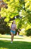 Glückliches Mädchen, das in Park läuft Lizenzfreies Stockfoto