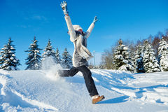 Glückliches Mädchen, das in Schnee im Winter springt Lizenzfreies Stockfoto