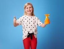 Glückliches Mädchen, das sich Daumen und und Sonnencreme auf Blau zeigt Lizenzfreie Stockfotos