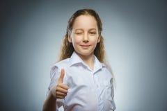 Glückliches Mädchen, das sich thub zeigt Nahaufnahme-Porträtkinderlächeln lokalisiert auf Grau Stockbild