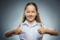 Glückliches Mädchen, das sich thubs zeigt Nahaufnahme-Porträtkinderlächeln lokalisiert auf Grau Lizenzfreie Stockfotos