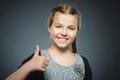 Glückliches Mädchen, das sich thubs zeigt Nahaufnahme-Porträtkinderlächeln lokalisiert auf Grau Lizenzfreies Stockbild