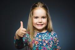 Glückliches Mädchen, das sich thubs zeigt Nahaufnahme-Porträtkinderlächeln lokalisiert auf Grau Stockbilder