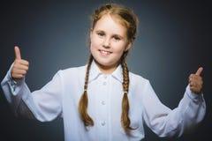 Glückliches Mädchen, das sich thubs zeigt Nahaufnahme-Porträtkinderlächeln lokalisiert auf Grau Stockfotografie
