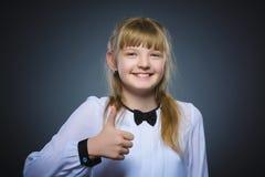 Glückliches Mädchen, das sich thubs zeigt Nahaufnahme-Porträtkinderlächeln lokalisiert auf Grau Lizenzfreies Stockfoto