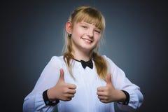 Glückliches Mädchen, das sich thubs zeigt Nahaufnahme-Porträtkinderlächeln lokalisiert auf Grau Stockfotos