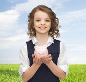 Glückliches Mädchen, das Sparschwein auf Palmen hält Lizenzfreie Stockfotos