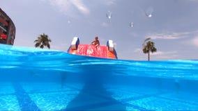 Glückliches Mädchen, das Swimmingpool im im Freien auf Sommerferien auf tropischem Strand spielt stock video