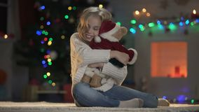 Glückliches Mädchen, das Teddybären in Sankt-Kostüm nahe schön verziertem Baum umarmt stock video