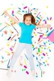 Glückliches Mädchen, das unter Haufen des farbigen Briefpapiers legt Stockfoto