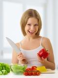 Glückliches Mädchen, das vegetarische Nahrung zubereitet Stockfotos