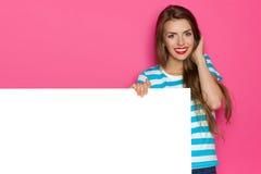 Glückliches Mädchen, das weißes Plakat zeigt stockbilder