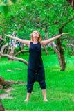 Glückliches Mädchen, das Yoga im Park tut Lizenzfreies Stockbild