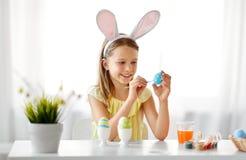 Glückliches Mädchen, das zu Hause Ostereier färbt lizenzfreie stockfotos