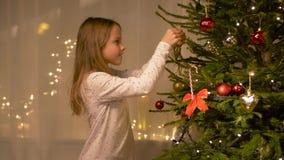 Glückliches Mädchen, das zu Hause Weihnachtsbaum verziert stock footage