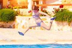 Glückliches Mädchen, das zum Pool springt stockfoto