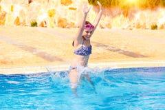 Glückliches Mädchen, das zum Pool springt lizenzfreie stockfotos