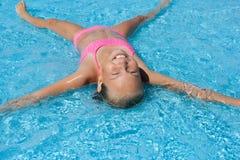 Glückliches Mädchen, das zurück auf ihr im Pool liegt Lizenzfreie Stockbilder
