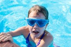 glückliches Mädchen in den blauen Schutzbrillen schwimmend im Swimmingpool Stockbilder