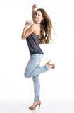 Glückliches Mädchen in den Jeans, die am Studio aufwerfen Lizenzfreie Stockfotos