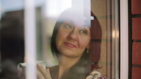 Glückliches Mädchen in den Pyjamas, die einen Tasse Kaffee sitzt auf dem Fensterbrett halten stock video footage