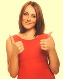 Glückliches Mädchen der jungen Frau zeigt Pluszeichendaumen ja, orange Dr. stockfotos