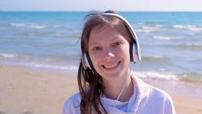 Glückliches Mädchen des Porträts, das Wege Musik in den Kopfhörern hören, rüttelt Hauptmeersandstrand stock video