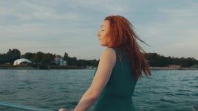 Glückliches Mädchen des roten Haares im Motorboot Genießen Sie Sommerabend unterhaltung landschaft stock footage