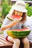 glückliches Mädchen des Sommers Kinder, welchesim urlaub die Wassermelone im Freien isst Stockbilder