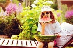 glückliches Mädchen des Sommers Kinder, welchesim urlaub die Wassermelone im Freien isst Stockfotos
