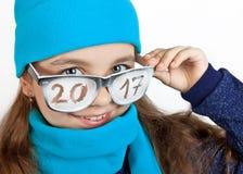 Glückliches Mädchen in einer Kappe und in einem Schal in den lustigen Gläsern mit der Aufschrift 2017 Lizenzfreies Stockfoto