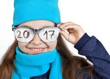 Glückliches Mädchen in einer Kappe und in einem Schal in den lustigen Gläsern mit der Aufschrift 2017 stockfotos