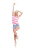 Glückliches Mädchen in gestreifter Spitze und in kurzer Jeanshose Stockfotografie
