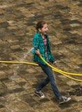 Glückliches Mädchen gießt Wasser von den Passanten eines Schlauches Stockfotos