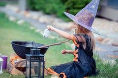Glückliches Mädchen in Halloween-Kostüm mit Steckfassungskürbis Trick oder Festlichkeit lizenzfreies stockbild