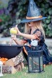 Glückliches Mädchen in Halloween-Kostüm mit Steckfassungskürbis Trick oder Festlichkeit lizenzfreie stockfotografie