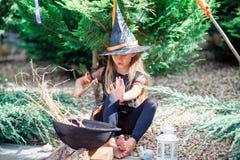 Glückliches Mädchen in Halloween-Kostüm mit Steckfassungskürbis Trick oder Festlichkeit lizenzfreie stockfotos