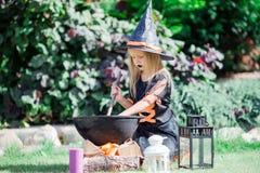 Glückliches Mädchen in Halloween-Kostüm mit Steckfassungskürbis Trick oder Festlichkeit lizenzfreie stockbilder