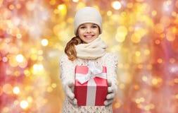 Glückliches Mädchen im Hut, im Schal und in den Handschuhen mit Geschenkbox lizenzfreies stockbild