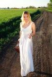 Glückliches Mädchen im Kleid mit dem Retro- Koffer, gehend auf einsame Straße Stockbilder
