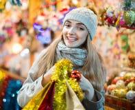 Glückliches Mädchen im Mantel, der am Weihnachtsmarkt aufwirft Stockbild