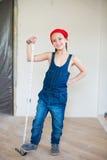 Glückliches Mädchen im roten Hut mit Reparaturausrüstungsrouletten Lizenzfreie Stockfotografie