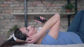 Glückliches Mädchen in Kopfhörer mit Smartphone finden Lieder Gefallen und singen bei auf Bett am Feiertag zu Hause sich entsp stock footage