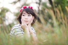 Glückliches Mädchen liegt unter den wilden Blumen an einem Sommerabend Lizenzfreie Stockfotos