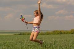 Glückliches Mädchen mit dem langen Haar, das eine farbige Windmühle und Sprünge hält lizenzfreies stockbild