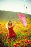 glückliches Mädchen mit dem rosa Regenschirm über rotem Mohnblumenfeld lizenzfreie stockfotos