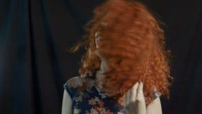 Glückliches Mädchen mit dem roten Haar auf einem schwarzen Hintergrund stock video footage