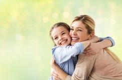 Glückliches Mädchen mit der Mutter, die über Lichtern umarmt Lizenzfreie Stockfotos