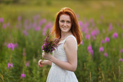 Glückliches Mädchen mit einem Blumenstrauß von Blumen Stockfoto